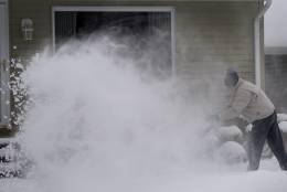 Bob Floerke clears snow from his front walkway near West Michigan in Saginaw Township, Mich., on Monday, Dec. 12, 2016. According to the National Weather Service, almost nine inches of snow fell on Saginaw on Sunday through Monday morning. All area schools are closed for the day. (Jeff Schrier/The Saginaw News via AP)