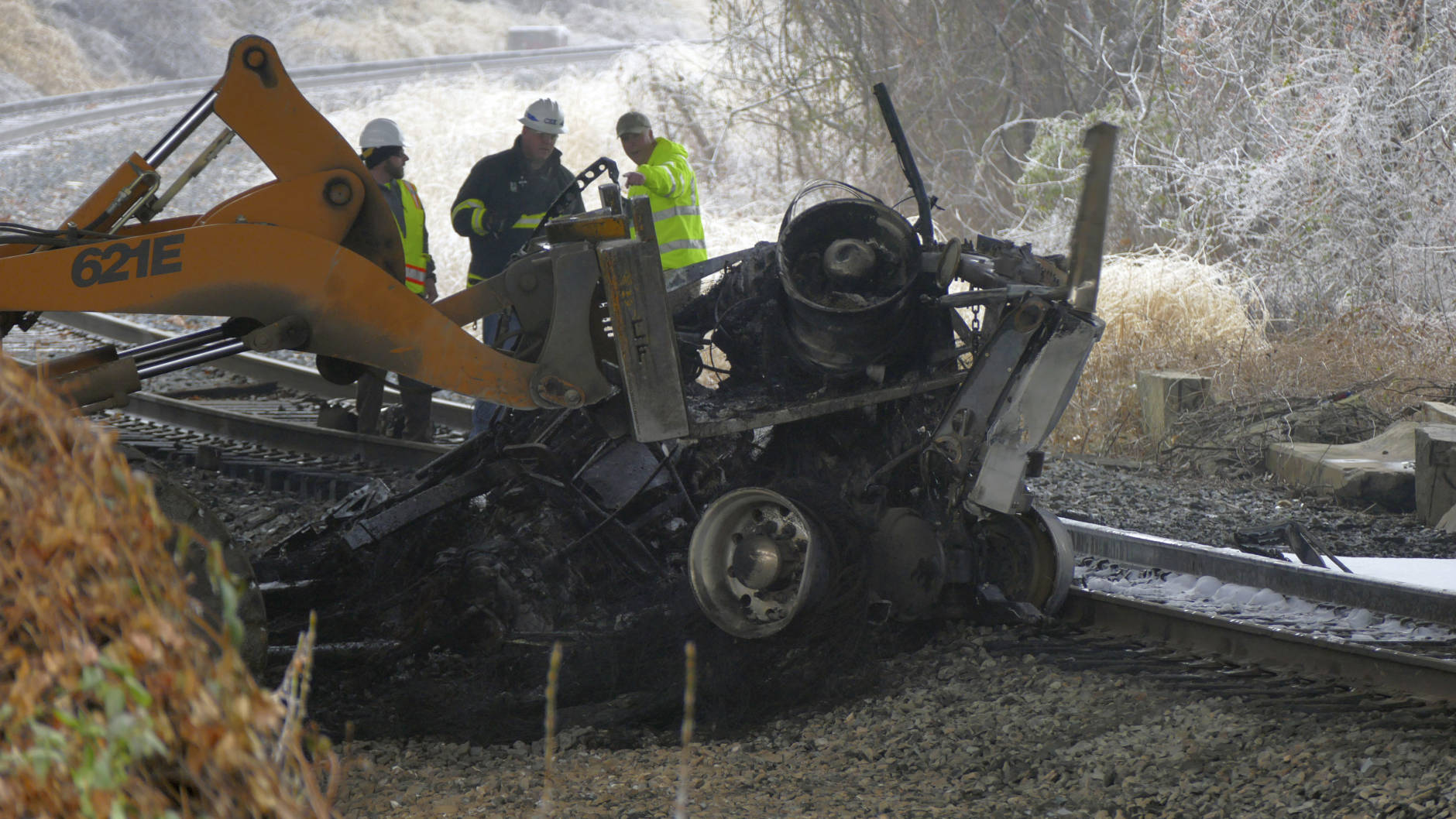 Seen from the Interstate 95 overpass from Grove Street in southwest Baltimore, Md., emergency workers extract the wreckage of a tractor trailer from railroad tracks after it fell off a bridge and exploded, in a series of accidents that shut down I-95 on Saturday, Dec. 17, 2016. An ice storm created slick conditions, sparking a chain reaction pile-up involving dozens of vehicles. (Karl Merton Ferron/The Baltimore Sun via AP)