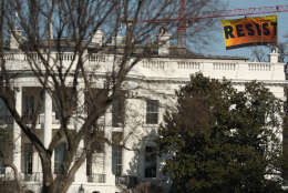 """A banner unfurled by Greenpeace demonstrators that reads """"Resist"""" is seen at the construction site of the former Washington Post building, near the White House in Washington, Wednesday, Jan. 25, 2017, after police say protesters climbed a crane at the site refusing to allow workers to work in the area.   (AP Photo/Andrew Harnik)"""