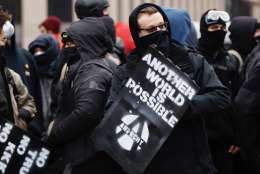 Masked anti-Trump protesters rally together at McPherson Square. (WTOP/Kate Ryan)