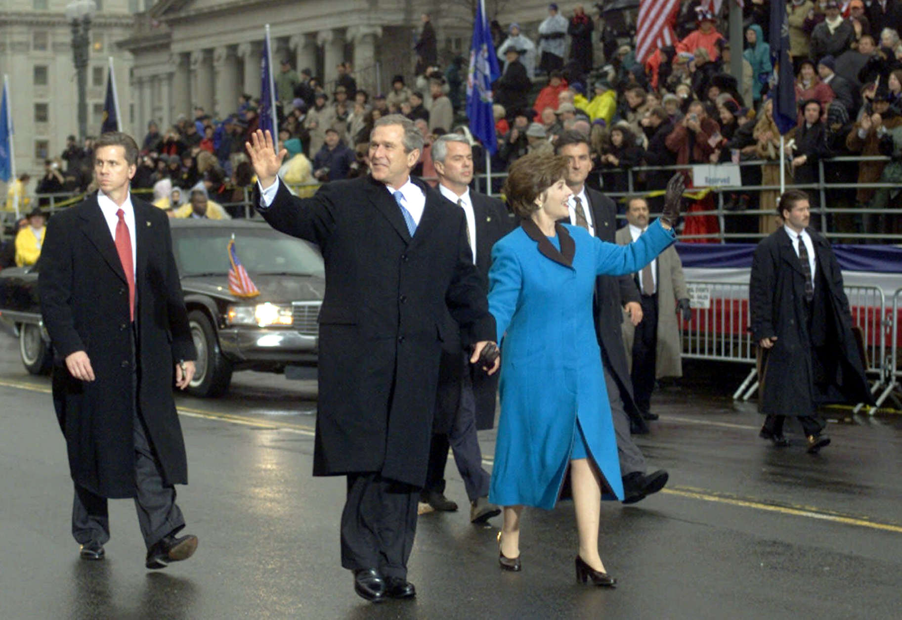 ** FILE ** With Secret Service agents accompanying them, President Bush and first lady Laura Bush wave as they walk down Pennsylvania Avenue during the Inaugural Parade in Washington  in this Jan. 20, 2001 file photo.   Security for the 2005 inauguration is expected to be the tightest in inaugural history.  (AP Photo/Doug Mills, File)
