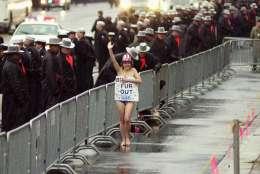 A topless protester runs past a police barricade along Pennsylvania Avenue during President Bush's inaugural parade Saturday, Jan. 20, 2001, in Washington. (AP Photo/Robert F. Bukaty)
