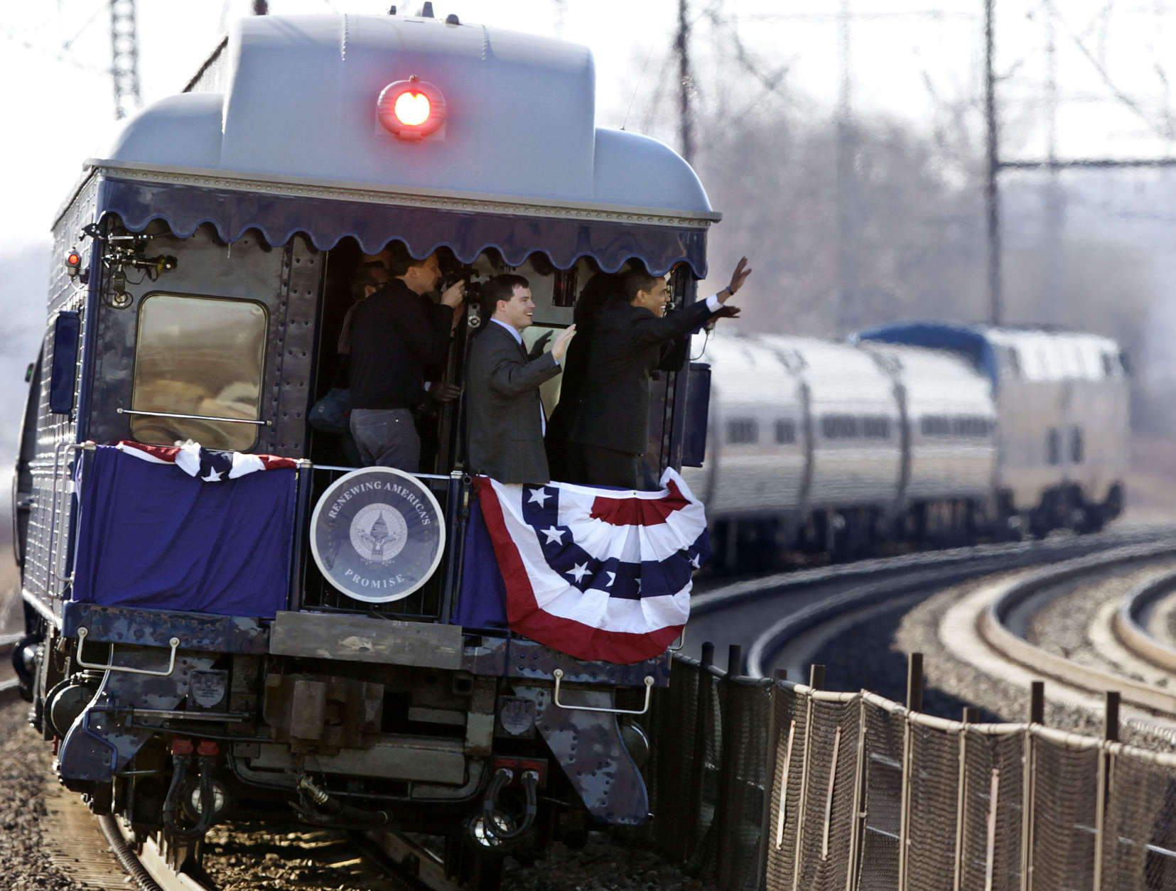 ** RE TRANSMITTED WITH ALTERNATE CROP **President-elect Barack Obama, far right, waves from the back of a train to the waiting crowd at the Claymont Amtrak rail station as it moves through Claymont, Del., Saturday, Jan. 17, 2009. (AP Photo/Carolyn Kaster)