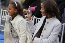 Malia Obama, 10, right, takes a picture as she sits next to her sister Sasha before their parents, President-elect Barack Obama and Michelle Obama, arrive onstage at the Lincoln Memorial inaugural concert Sunday, Jan. 18, 2009. (AP Photo/Charles Dharapak)