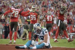 Carolina Panthers tight end Greg Olsen (88) sits dejected in the end zone as the Tampa Bay Buccaneers celebrate after the Panthers failed on a 2-point conversion during the fourth quarter of an NFL football game Sunday, Jan. 1, 2017, in Tampa, Fla. The Buccaneers won the game 17-16. (AP Photo/Phelan M. Ebenhack)