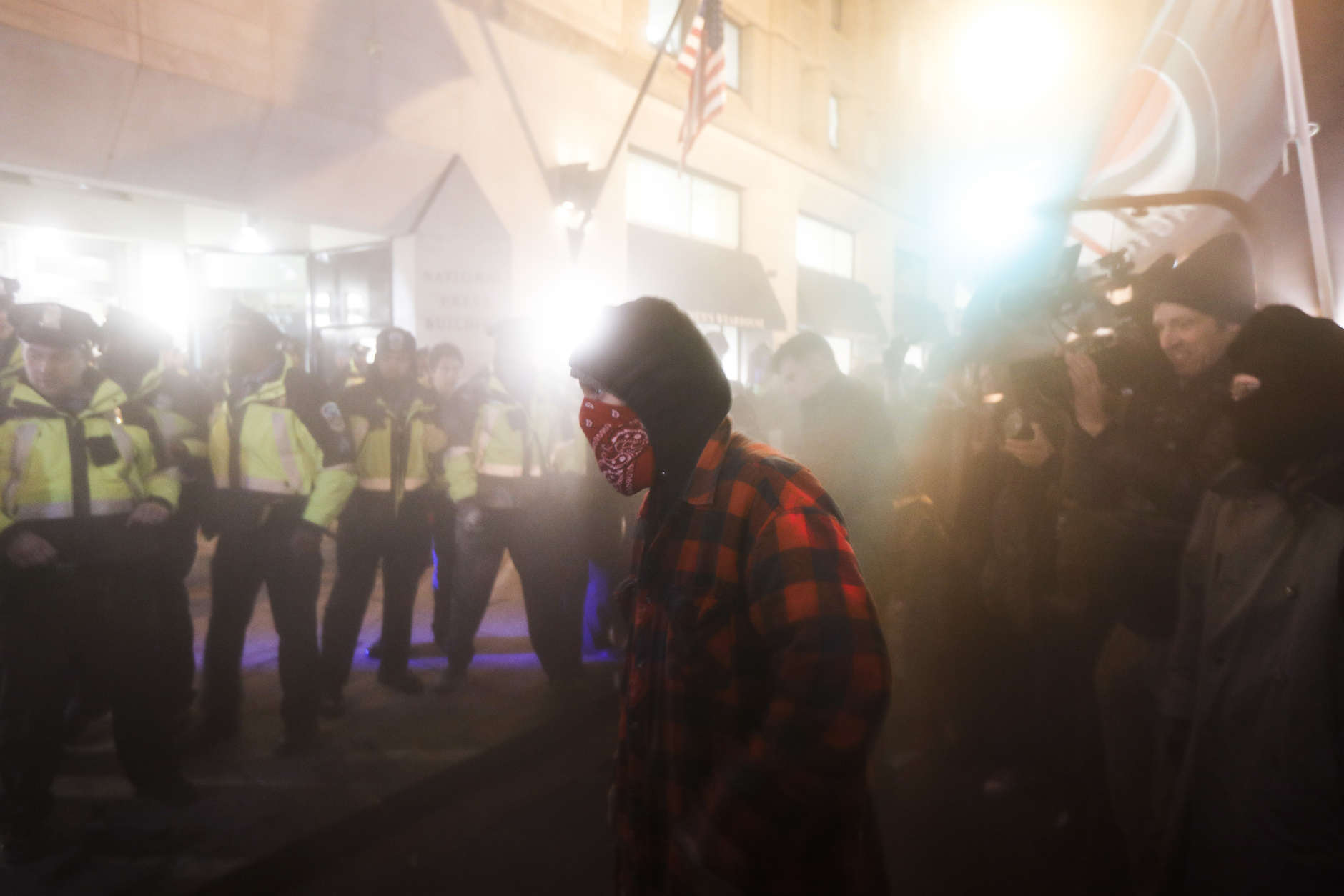 A protester walks through a cloud of gas sprayed by police following outside the National Press Club Thursday, Jan. 19, 2017, in Washington. (AP Photo/John Minchillo)