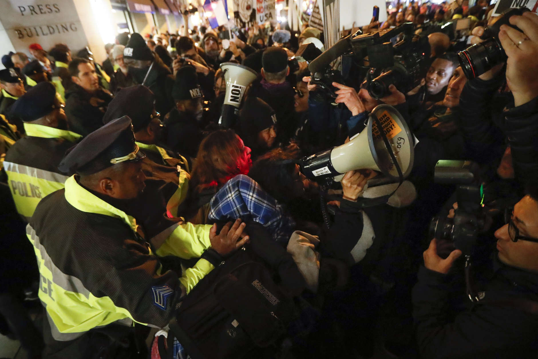 Protesters scuffle with police after refusing to vacate the sidewalk in front of the National Press Club Building ahead of the presidential inauguration, Thursday, Jan. 19, 2017, in Washington. (AP Photo/John Minchillo)
