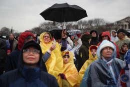 Spectators wait in the rain on the National Mall in Washington, Friday, Jan. 20, 2017, before the presidential inauguration of Donald Trump. (AP Photo/John Minchillo)