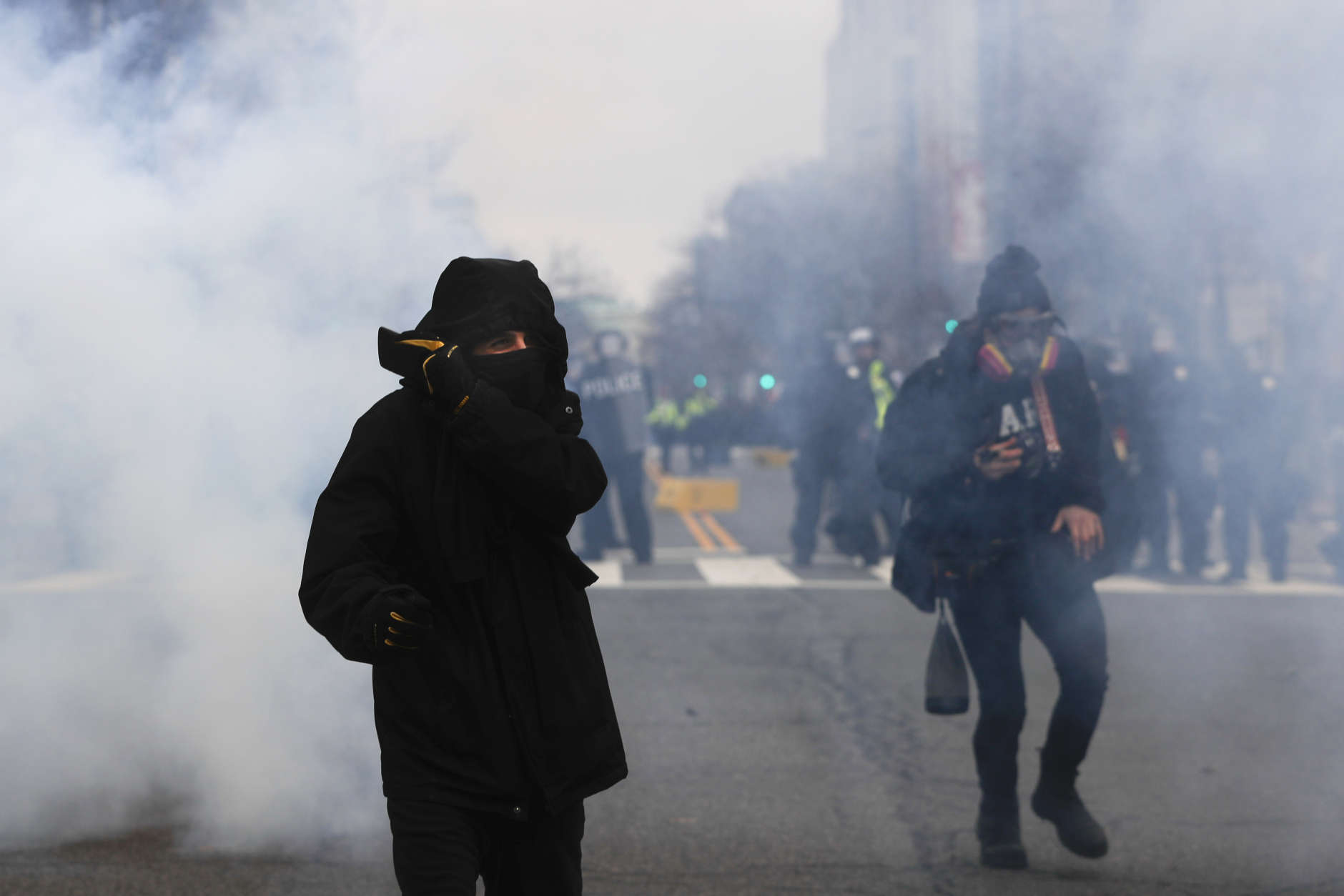 A protester shields his mouth and nose from gas fired by police during a demonstration after the inauguration of President Donald Trump, Friday, Jan. 20, 2017, in Washington. (AP Photo/John Minchillo)