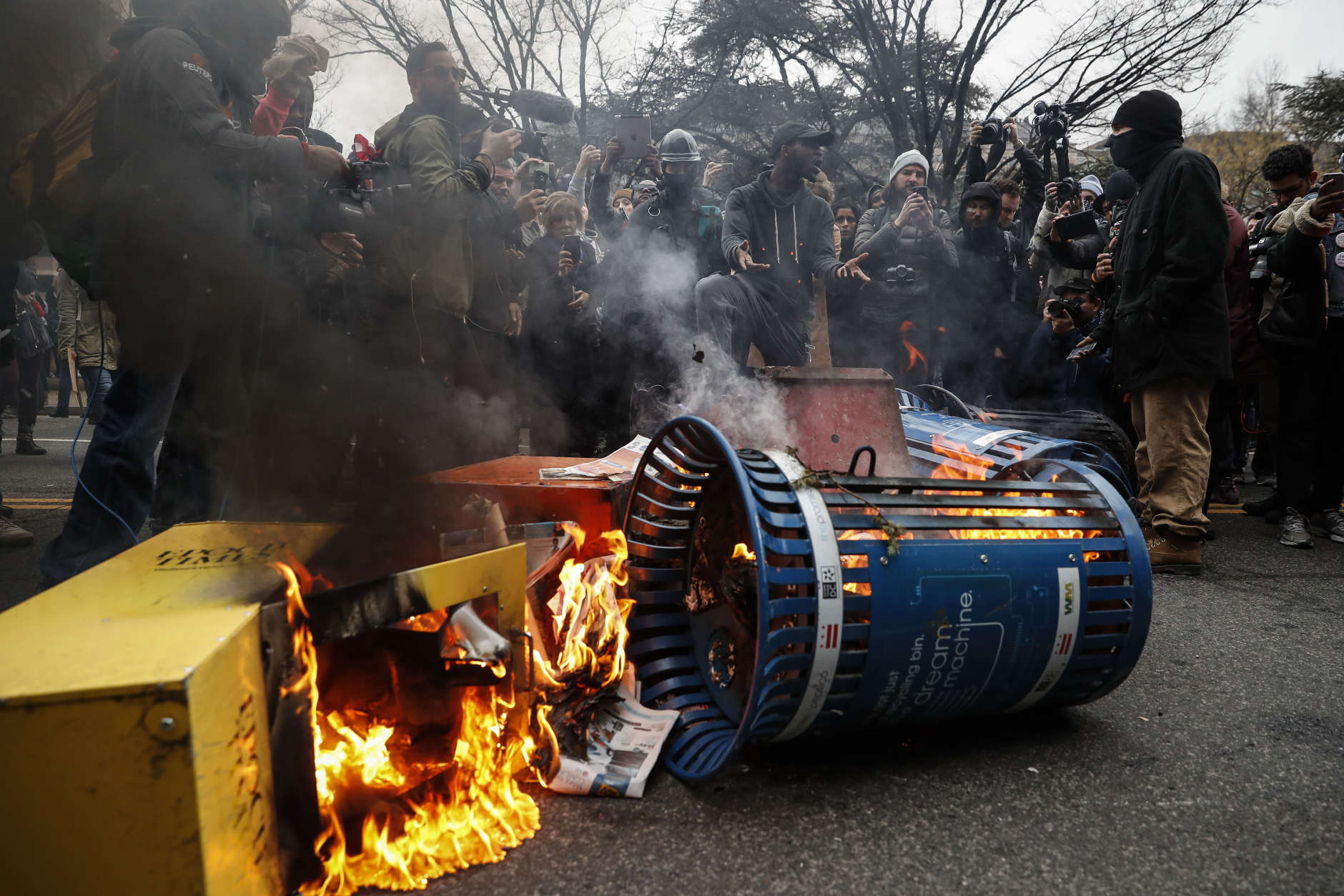 A Washington resident, center right, demands peace as he guards a pile of burning newspaper machines to prevent protestors from feeding the flames during a demonstration after the inauguration of President Donald Trump, Friday, Jan. 20, 2017, in Washington. (AP Photo/John Minchillo)