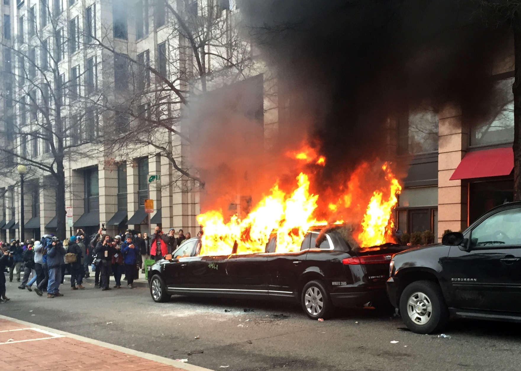 Protesters set a parked limousine on fire in downtown Washington, Friday, Jan. 20, 2017, during the inauguration of President Donald Trump. Protesters registered their rage against the new president Friday in a chaotic confrontation with police who used pepper spray and stun grenades in a melee just blocks from Donald Trump's inaugural parade route. Scores were arrested for trashing property and attacking officers. (AP Photo/Juliet Linderman)