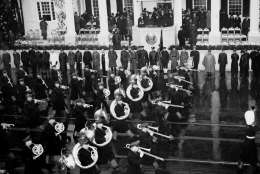 President Franklin D. Roosevelt smiles in appreciation as a brass marching band files by during the rain-swept second inaugural parade in Washington, D.C., Jan. 20, 1937. (AP Photo)