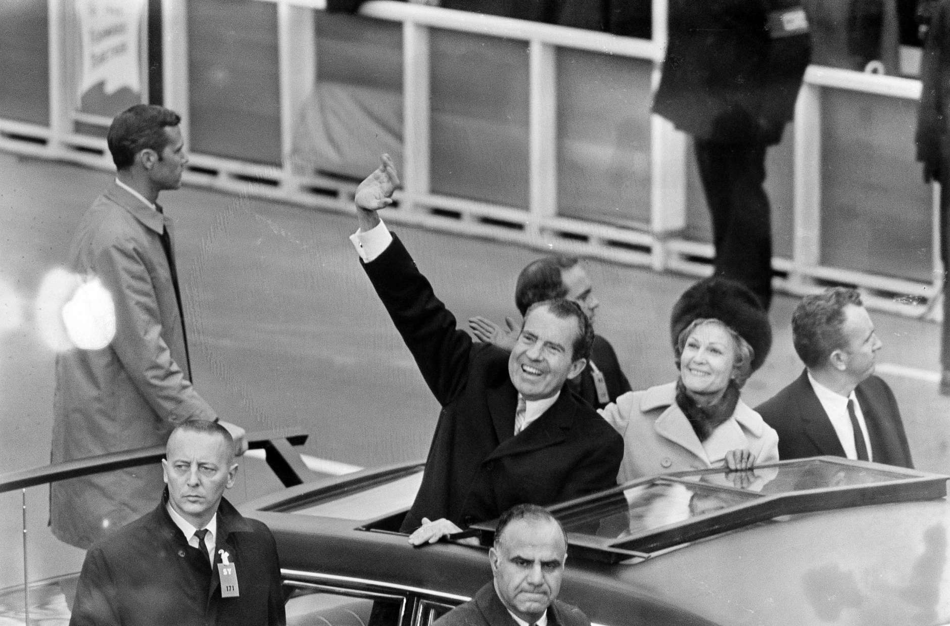 President Nixon waves as he and First Lady Pat Nixon stand in the limousine carrying them from the inauguration at the Capitol to the White House in Washington, D.C., Jan. 20, 1969. Secret Service agents are seen alongside the car. (AP Photo)