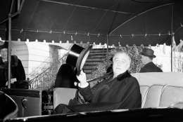A cape draped over his shoulder, President Franklin D. Roosevelt doffs his silk topper as he leaves the White House, Washington, D.C.,, Jan. 20, 1941 to attend special church services before taking his third term oath at the capitol. (AP Photo)