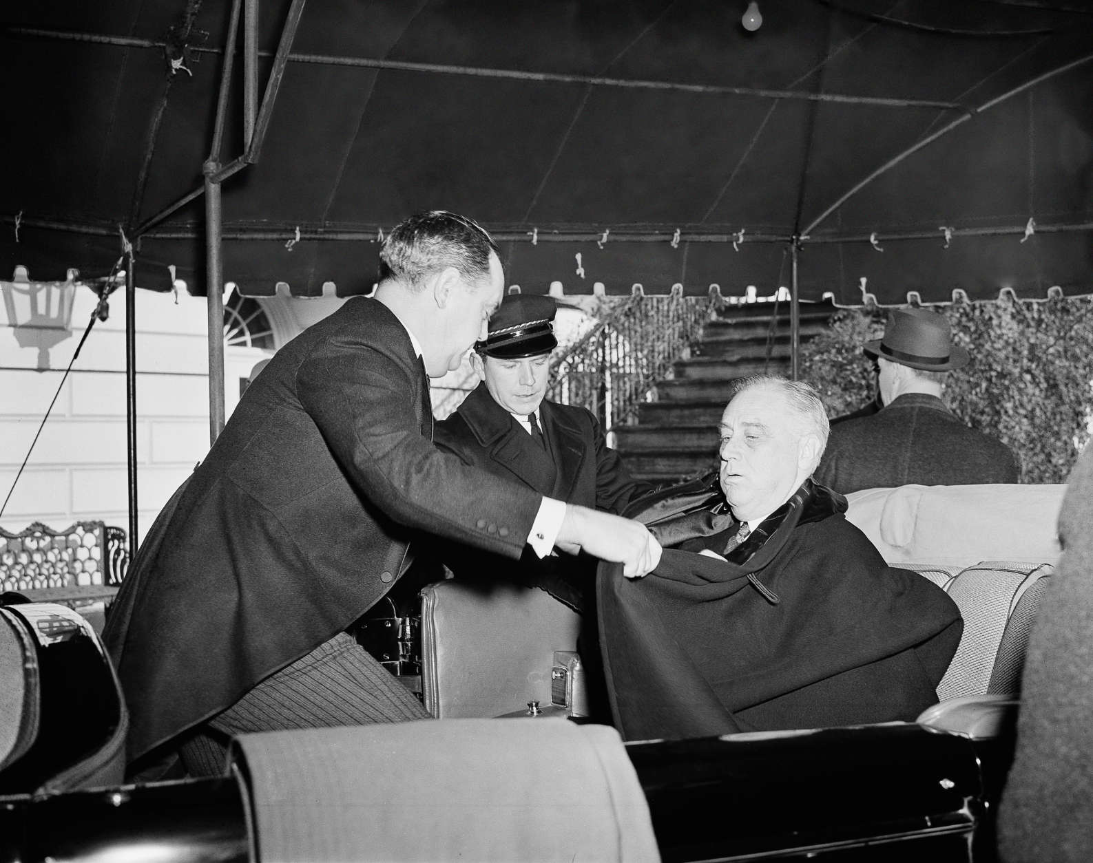 The temperature was near freezing so President Franklin D. Roosevelt was wrapped up well in his cloak by his bodyguard, Thomas Qualters, as the president left for church services in Washington, Jan. 20, 1941, before his third inauguration. (AP Photo)