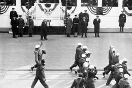 President Franklin Roosevelt and a squadron of WPA workers attired in overalls exchange hand waves and greetings as the WPA men passed the presidential reviewing stand during the Inaugural parade in Washington on Jan. 20, 1941. Vice President Wallace at right of president?s group smiles. (AP Photo)
