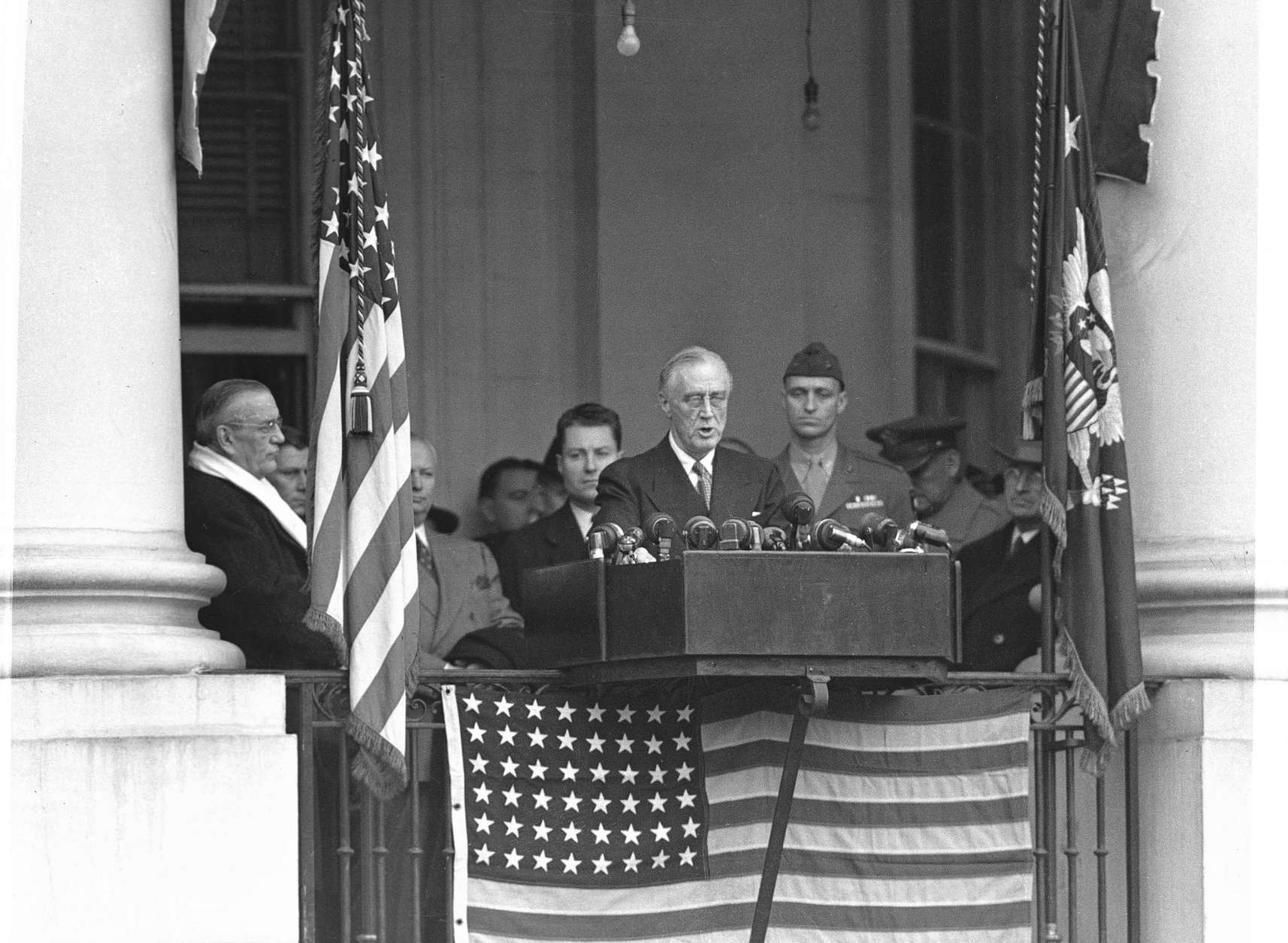 "Delivering a brief inaugural address from the portico of the White House, President Franklin D. Roosevelt calls for ""a durable peace,"" Jan. 20, 1945. Others, from left: Edwin Halsey, Secretary of State; three unidentified Secret Service agents; Col. James Roosevelt USMCR; Maj. Gen. Edwin Watson, partially obscured; and Vice President Harry S. Truman. (AP Photo)"