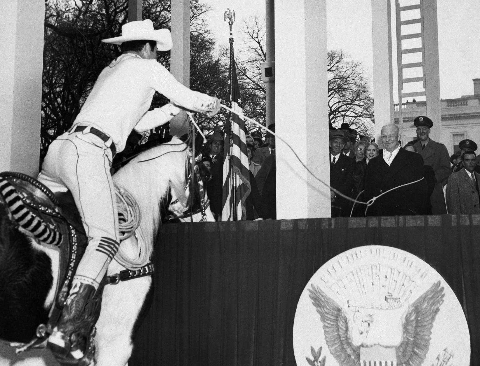 Dwight D. Eisenhower, center, seems to be getting a big kick out of being lassoed by Monte Montana, dressed in cowboy style, as he reviewed the inaugural parade from presidential stand in front of the White House, Jan. 20, 1953, Washington, D.C. (AP Photo)