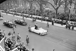 President Dwight Eisenhower, in his open car, waves to cheering spectators as he approaches the White House where he went into reviewing stand to watch the inaugural parade in Washington, Jan. 20, 1953. Crowds line Pennsylvania Avenue sidewalk. (AP Photo)