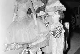 With a princely gesture, circus midget Prince Paul presents flowers to three English girls who are in the show, backstage during the New York run, April 14, 1953. The girls are: left to right, Pat Cooper, who is from Devonshire; Shiley Coomas and Brinda Elliot, both of London. (AP Photo/VN)