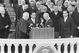 President Dwight D. Eisenhower was all smiles as he lowered his hand for a handshake with Chief Justice Earl Warren at end of public oath-taking for second term of office at Capitol in Washington, Jan. 21, 1957. In center is John Fey, clerk of the Supreme Court, who held Bible for the ceremony. (AP Photo)