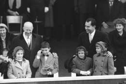 President Dwight D. Eisenhower regards with an amused smile the embarrassed salute given by his grandson, David, to a passing unit of the inaugural parade in Washington, Jan. 21, 1957. Vice President Richard  Nixon and his oldest daughter, Patricia, right, share the fun. David's sister, Barbara, is at left, and Vice President Nixon's youngest daughter, Julie, watches the paraders. (AP Photo)