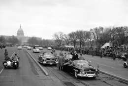 President Dwight Eisenhower stands in his open car and waves as he leaves the Capitol just before swinging into Constitution Avenue on traditional inaugural parade route in Washington on Jan. 21, 1957. (AP Photo)