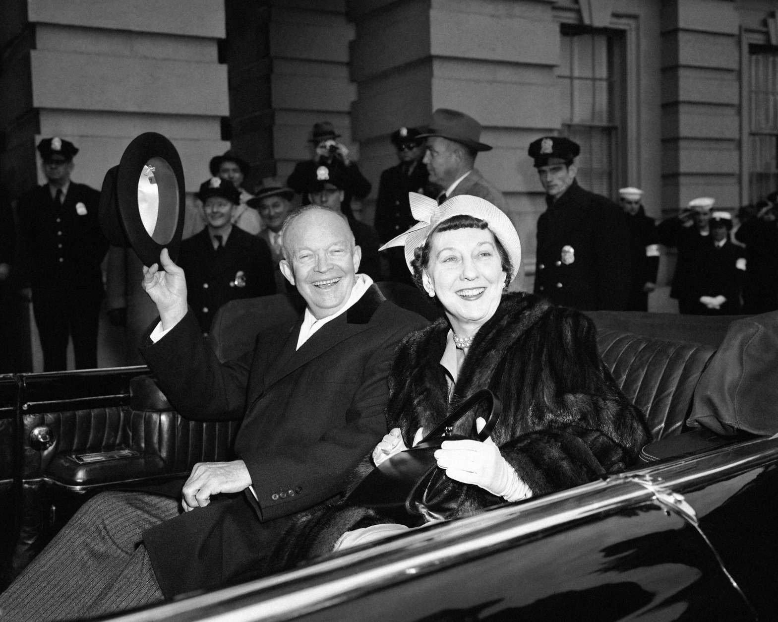 President Dwight Eisenhower and Mrs Mamie Eisenhower sit  in the open car and wave as they  leave the Capitol in Washington Jan. 21, 1957, just before swinging into Constitution Avenue on traditional inaugural parade route. (AP Photo)
