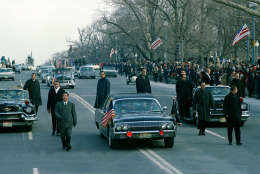 The motorcade carrying President-elect Lyndon B. Johnson and his wife Lady Bird Johnson is shown en route to the Capitol building as secret service agens run alongside of closed car in Washington, D.C., Jan. 20, 1965.  Johnson will be sworn in as the 36th president of the United States.  (AP Photo)