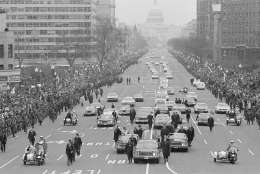 The motorcade carrying President-elect Nixon and President Johnson to the inaugural ceremony drives down Pennsylvania Avenue toward the U.S. Capitol in Washington, Jan. 20, 1969.  The incoming and outgoing chief executives are in the flag-decked car flanked by the Secret Service cars. (AP Photo)