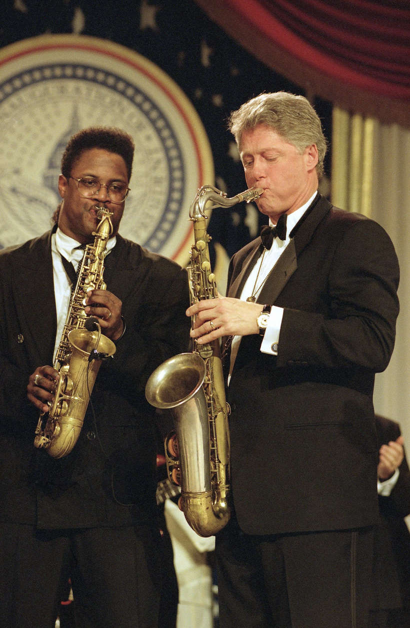 """FILE - In this Jan. 20, 1993, file photo, President Bill Clinton plays the saxophone at the Arkansas ball on Inauguration Day, Jan. 20, 1993. The inauguration of the U.S. president is traditionally a highly-scripted celebration, with seating charts, schedules, dress rehearsals, and planning committees that map each moment of the history-making day from start to finish. But sometimes the unexpected happens. On inauguration night, the new president delighted thousands at a packed room at the Arkansas ball, where Clinton played his trademark saxophone as Ben E. King sang, """"Your Momma Don't Dance and Your Daddy Don't Rock 'n' Roll.""""  (AP Photo/Greg Gibson, File)"""