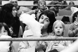 Former Beatle Paul McCartney samples his young daughter Stella's cotton candy as the two sit on the sidelines at New York's Madison Square Garden, March 30, 1974, watching the Ringling Bros. & Barnum and Bailey Circus. (AP Photo/Suzanne Vlamis)