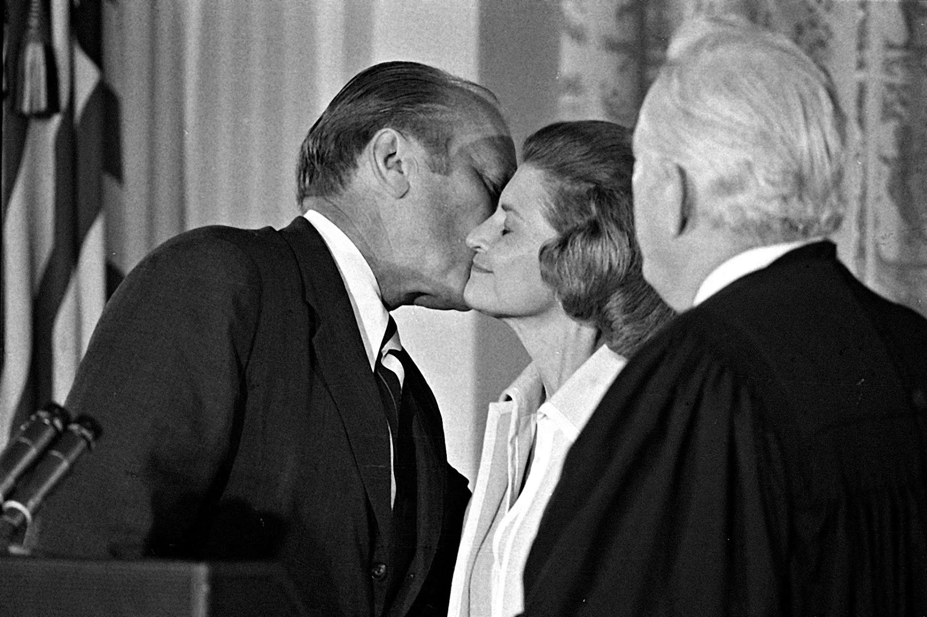 President Gerald R. Ford kisses his wife Betty, Aug. 9, 1974, after he was sworn in as 38th President of the United States by Chief Justice Warren Burger, right, in the East Room of the White House.  (AP Photo)