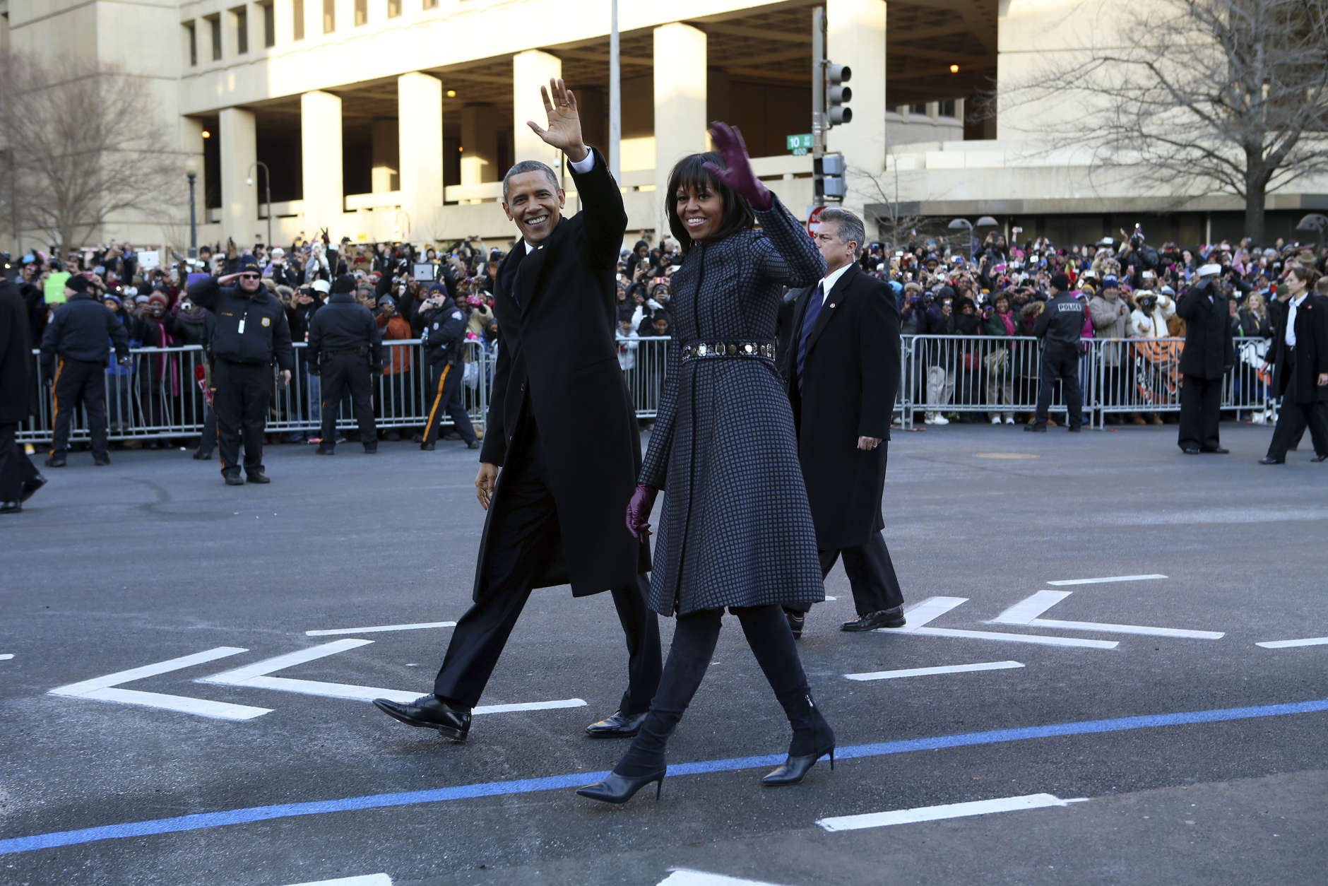 President Barack Obama and first lady Michelle Obama wave as they walk down Pennsylvania Avenue in Washington, Monday, Jan. 21, 2013, during the inaugural parade route , after his ceremonial swearing-in on Capitol Hill during the 57th Presidential Inauguration. (AP Photo/New York Times, Doug Mills, Pool)