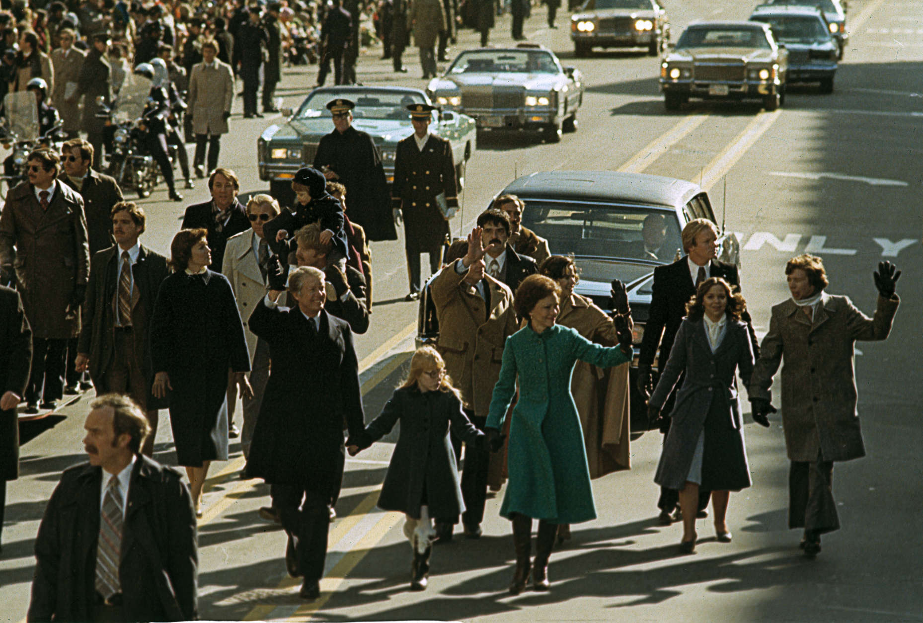 U.S. President Jimmy Carter, left, waving, first lady Rosalynn Carter hold hands with their daughter Amy as they take part in the inaugural parade in Washington, D.C., Jan. 20, 1977.   They are joined by other family members.  Carter was sworn in as the nation's 39th president during the inauguration ceremonies.  (AP Photo)