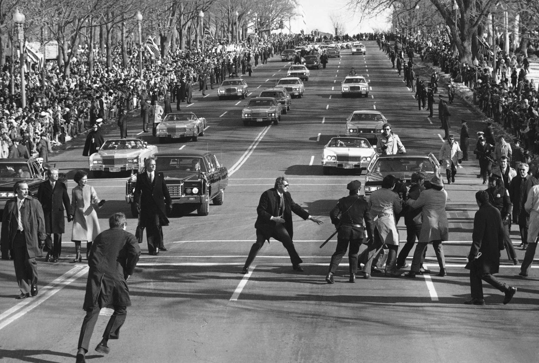 President Jimmy Carter and first lady Rosalynn watch, left, as police and Secret Service officials remove a spectator, right, who burst into the Inaugural Parade on Pennsylvania Avenue Thursday, Jan. 20, 1977 in Washington. (AP photo)