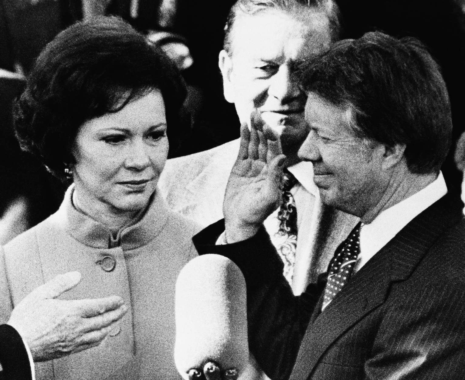 Rosalynn Carter, left, looks up at her husband Jimmy Carter as he takes the oath of office as the 39th President of the United States at the Capitol, Thursday, Jan. 20, 1977, Washington, D.C. Mrs. Carter held a family Bible for her husband. (AP Photo)