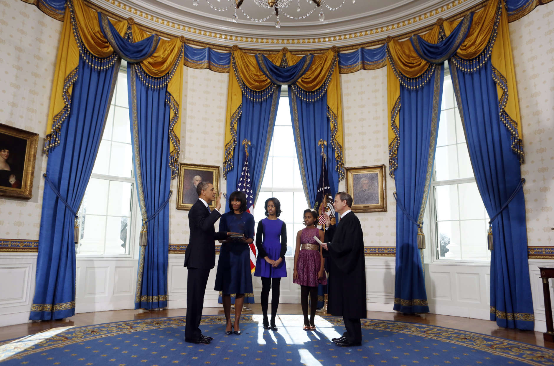 President Barack Obama is officially sworn-in by Chief Justice John Roberts in the Blue Room of the White House during the 57th Presidential Inauguration in Washington, Sunday, Jan. 20, 2013. Next to Obama are first lady Michelle Obama, holding the Robinson Family Bible, and daughters Malia and Sasha. (AP Photo/Larry Downing, Pool)