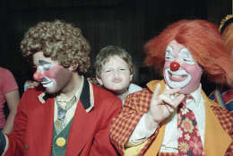 Kevin Thompson, celebrating his fourth year in Ringling Bros. Barnum and Bailey's famed Clown Alley, watches as 9-year-old Jonathon Young tries his hand at clowning during a visit by the circus troupe to Temple Beth Solomon of the Deaf in Arleta, California, Sept. 14, 1984. (AP Photo/Liu Heung Shing)