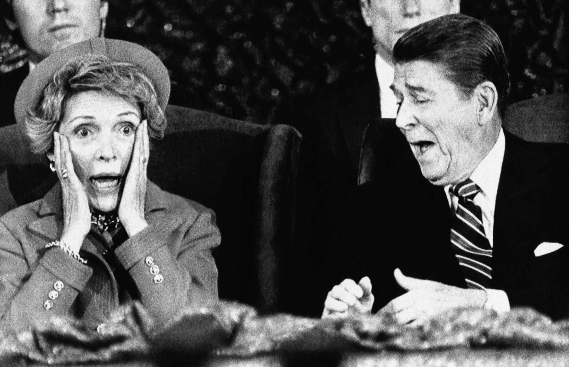 President  Ronald Reagan and wife Nancy  react after Mrs. Reagan sat down after speaking and forgot to introduce the President at the Capital Center in Landover, Md., Monday, Jan. 21, 1985, during an event held for those who would have participated in the inaugural parade, which was canceled because of bad weather. (AP Photo/Scott Stewart)