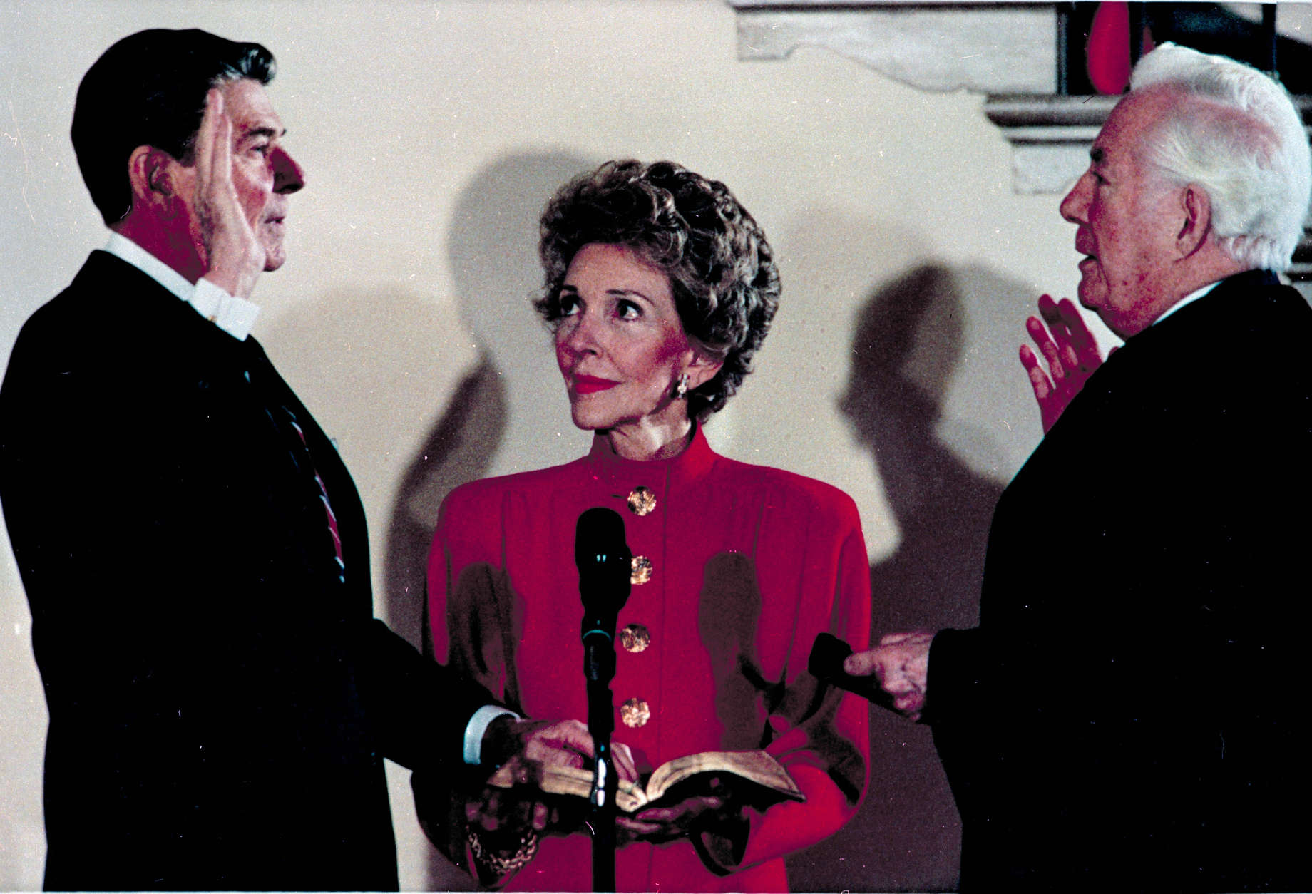 President Ronald Reagan takes the oath of office administered by Chief Justice Warren Burger in a private White House ceremony for a second term in Washington, D.C., Sunday, Jan. 20, 1985.  First Lady Nancy Reagan holds the bible.  (AP Photo/Ira Schwarz)