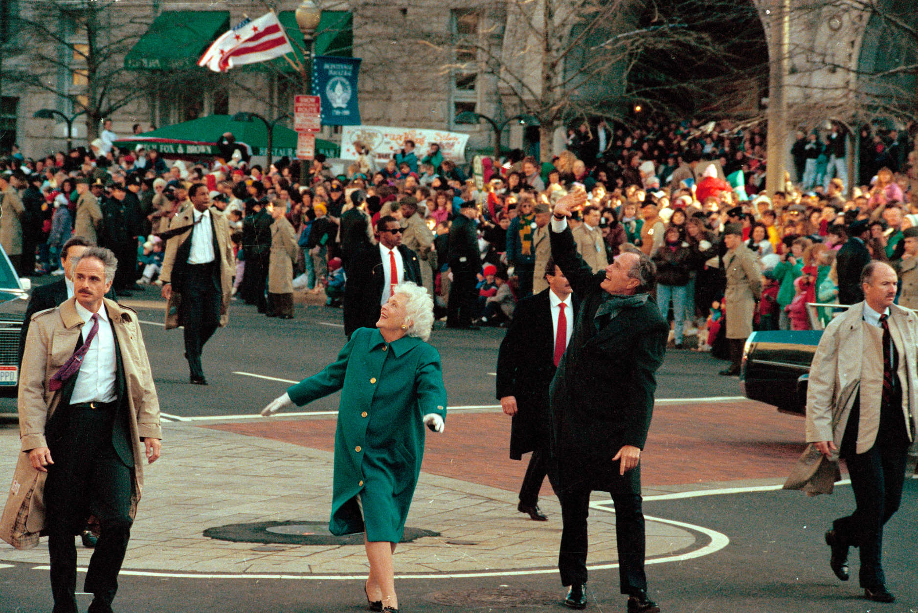 President George Bush, right, and his wife, first lady Barbara Bush, acknowledge the crowd on Pennsylvania Avenue after getting out of their limousine and walking the inaugural parade route in Washington, D.C., Friday, Jan. 20, 1989.  Earlier, Bush was sworn in as the 41st president of the United States.  (AP Photo/Dennis Cook)