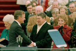 President George Bush, left, is congratulated by outgoing President Ronald Reagan after Bush took the oath of office as the 41st president of the United States on Capitol Hill in Washington, D.C., Friday, Jan. 20, 1989.  Shown at left is first lady Barbara Bush and applauding at right is Nancy Reagan.  (AP Photo/Bob Daugherty)