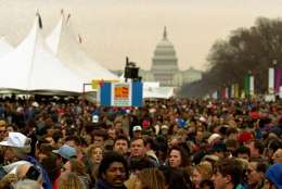"""Thousands gather on the Mall Sunday to take in """"America's Reunion on the Mall"""", a free festival of arts, crafts and music that opens Bill Clinton's five-day inaugural celebration.  The Capitol is in the background.  (AP Photo/Mark Wilson)"""