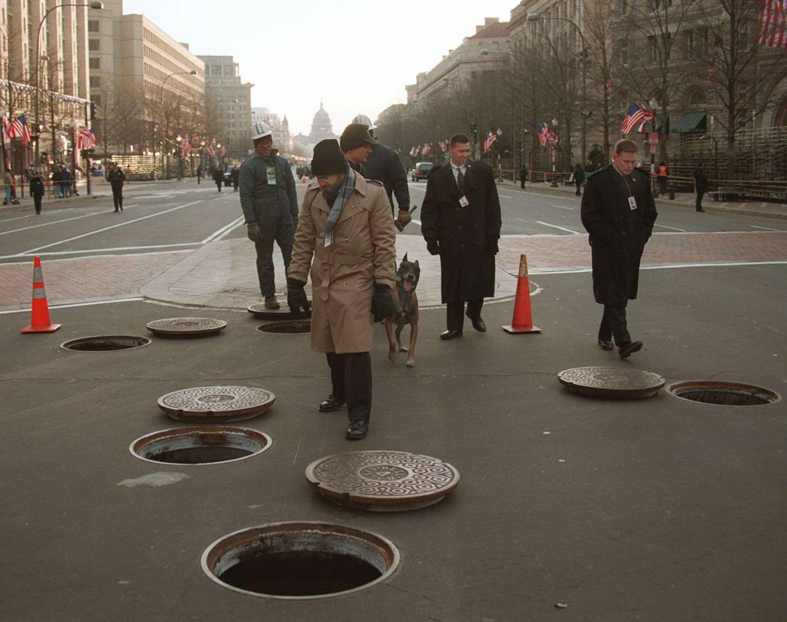 U.S. Secret Service agents check manholes on Pennsylvania Avenue in Washington Monday Jan. 20, 1997 in anticipation to President Clinton's inaugural parade. (AP Photo/Mark Wilson)