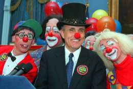 New York City Mayor Rudolph W. Giuliani, center, doffed with a red clown nose and ringmaster's top hat, is joined by Ringling Brothers Barnum and Bailey Circus clowns Chris Allison, left, and Karen DeSanto, right, at City Hall Tuesday, Feb. 23, 1999, in New York.  (AP Photo/Marty Lederhandler)