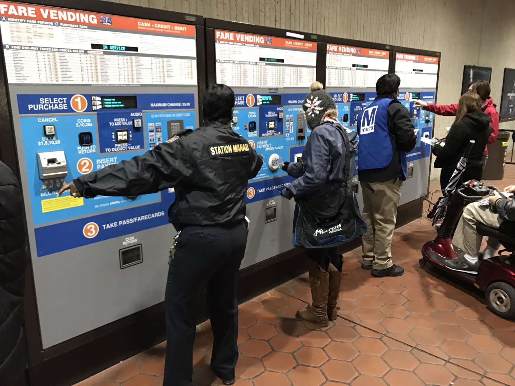 A Metro station manager helps customers navigate the fare machines early Friday morning for people looking to get around the District via Metro on Inauguration Day. An All Day Pass costs $14.50. (WTOP/Neal Augenstein)