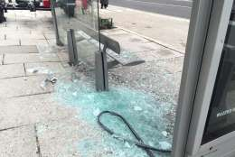Protesters damage a bus stop on 13th Street NW. (WTOP/Dennis Foley)