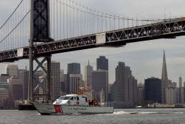 SAN FRANCISCO, CA - MARCH 25, 2003:  With the San Francisco skyline in the background a United States Coast Guard ship travels under the Oakland/San Francisco Bay Bridge on a routine Homeland Security mission March 25, 2003.  Security in the U.S. has been increased since the start of the war with Iraq.  (Photo by David Paul Morris/Getty Images)