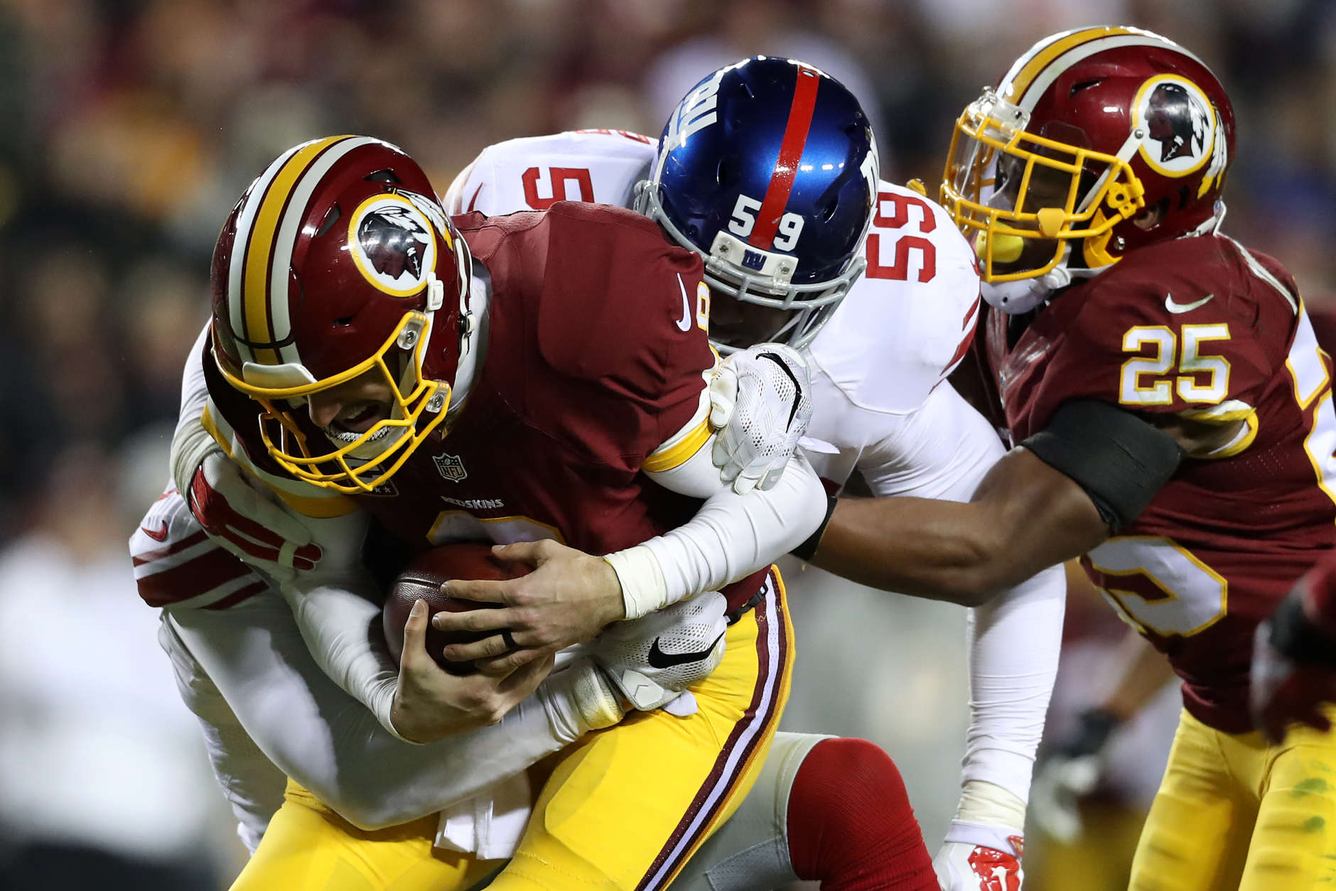 LANDOVER, MD - JANUARY 01: Quarterback Kirk Cousins #8 of the Washington Redskins is sacked by defensive back Leon Hall #25 and outside linebacker Devon Kennard #59 of the New York Giants in the third quarter at FedExField on January 1, 2017 in Landover, Maryland. (Photo by Rob Carr/Getty Images)
